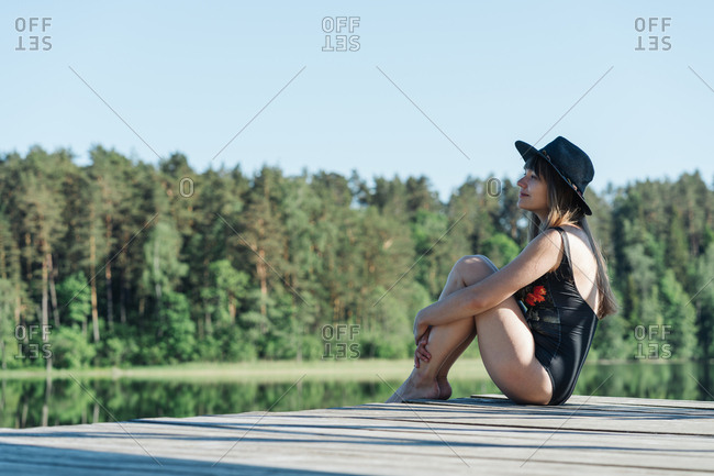 Side view of happy young woman in black swimsuit and hat sitting on wooden pier and admiring view of lake on clear blue sky and forest background