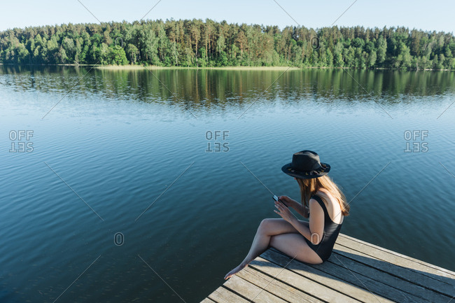 Side view of young woman in black swimsuit and hat sitting on wooden pier on the mobile phone on a lake on clear blue sky and forest background