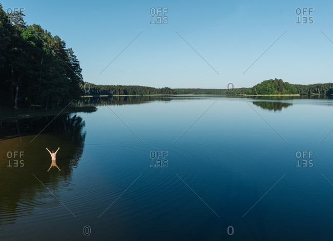 Scenic view of blue sky and large clear lake surrounded by dense forest with bathing unrecognizable person raising hands up