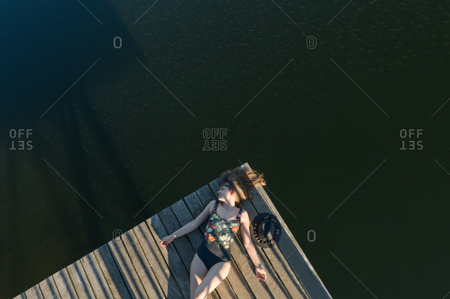 Top view of beautiful woman in black swimsuit and hat lying down on wooden pier of lake on clear blue sky and forest background