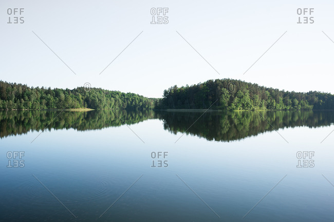 Scenic view of blue sky and large clear lake surrounded by dense forest
