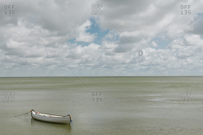 Picturesque view of white empty boat floating on calm surface of sea water on cloudy day