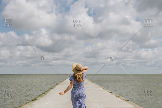 Back view of adult woman in straw hat and sundress running on empty concrete quay on cloudy day
