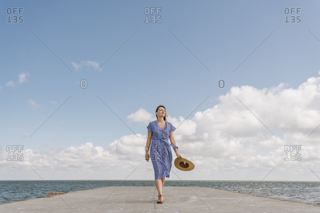 Back view of adult woman in straw hat and sundress on empty concrete quay on cloudy day