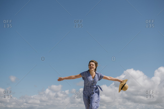 Content adult woman with blowing hair and in sundress walking with straw hat in hand on cloudy sky background
