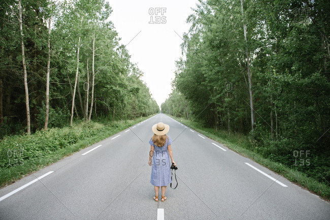 Back view of adult woman in straw hat and dress with camera standing in middle of drive way among tall green trees