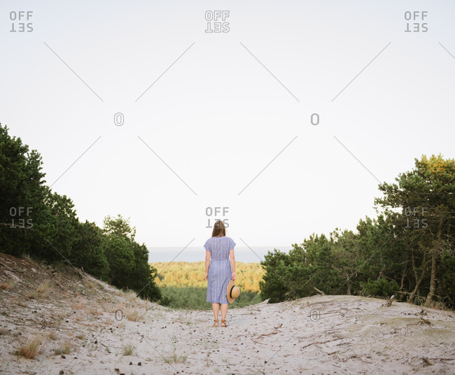 Back view of carefree adult woman in straw hat and sundress walking along forest road between pines at sunny day