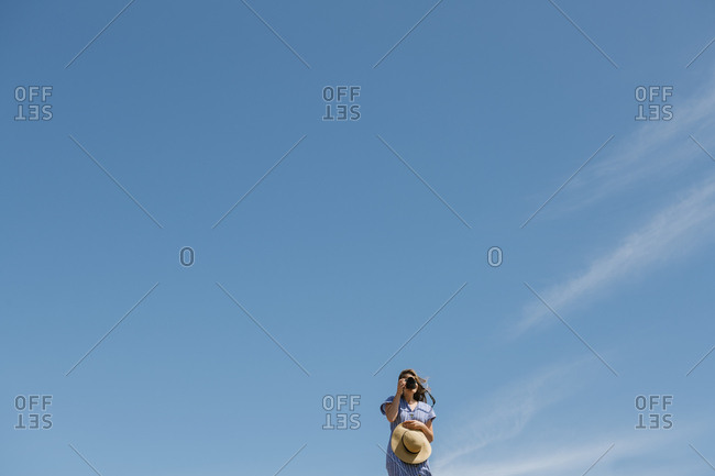 Woman in straw hat and dress using camera standing on sunny windy day with clear blue sky on background