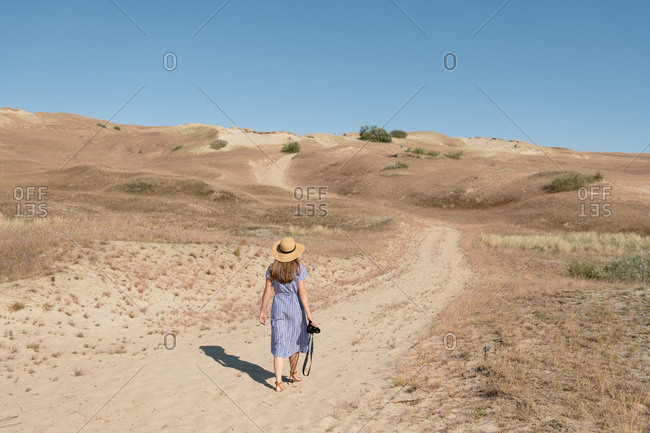 Back view of adult woman in straw hat and dress with camera walking on unpaved road among dry dusty field on sunny day