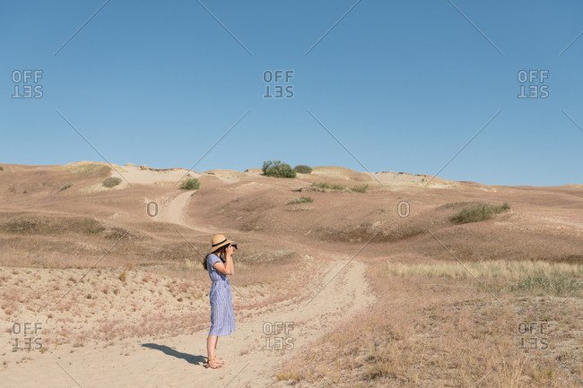 Back view of adult woman in straw hat and dress with camera taking photo on unpaved road among dry dusty field on sunny day