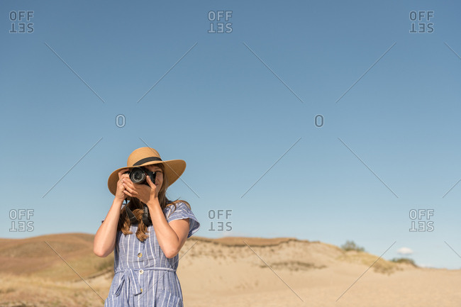 Adult woman in straw hat and dress with camera taking photo on sand dune of beach in a sunny day