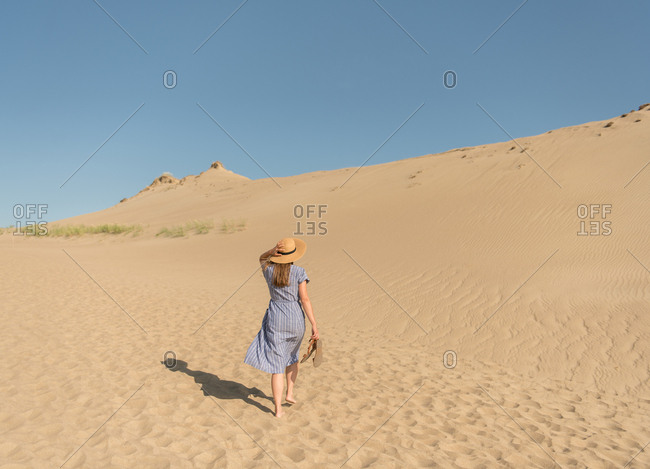 Adult woman in casual dress and straw hat walking having good time on sand dune on hot summer day