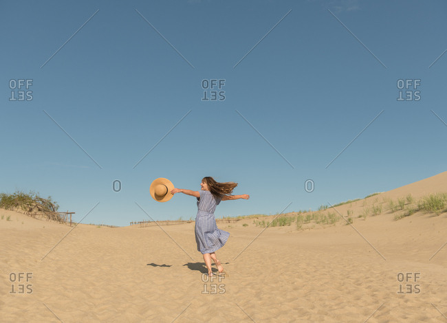 Adult woman in casual dress and straw hat running having good time on sand dune on hot summer day