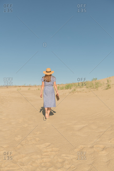 Thoughtful adult woman in casual dress and straw hat standing with book on sand dune on hot summer day