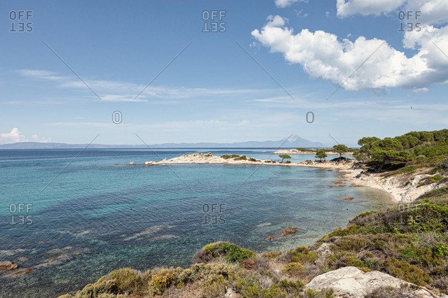Picturesque view of hilly green coast with transparent turquoise calm water in bright sunlight, halkidiki, greece