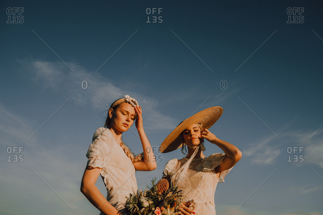 From below slim tanned women in wreath and straw hat with bunch of flowers on background of blue sky