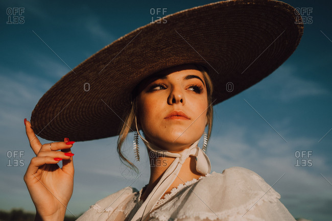 Beautiful stately woman in hats in bright sunny day