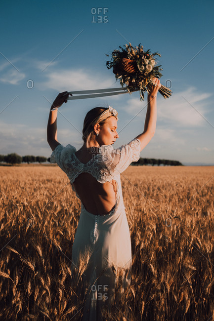 Back view of graceful tender woman in lace dress holding summer flower in raised hands in midday sun in wheat field