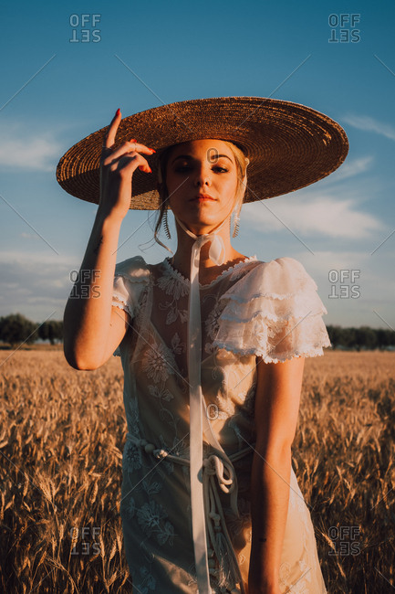 Woman in big round hat in middle of wheat field