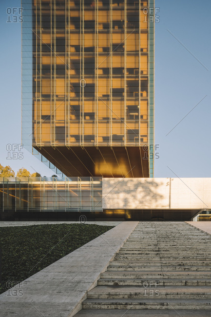 Madrid, Spain - January 2, 2019: Stylish glass skyscraper reflecting sun in bright day in downtown