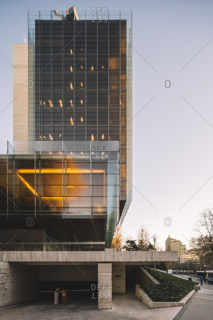 Madrid, Spain - January 2, 2019: Stylish glass skyscraper with parking reflecting sun in bright day in downtown