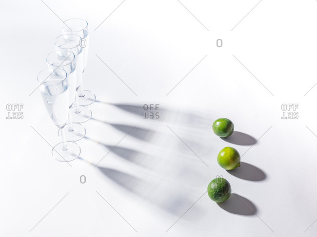 Contrasting shadows from glasses of water and green ripe limes on white background