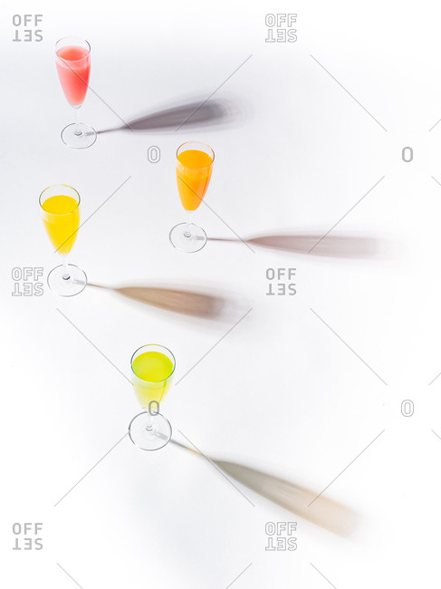 Contrasting shadows from glasses of juicy appetizing orange red yellow green drinks on white background