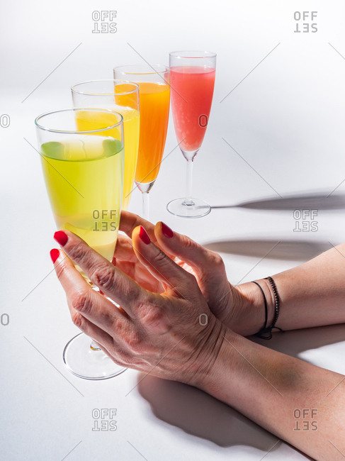 Woman crop hands holding a glass of juicy appetizing yellow near orange and red drinks on white background