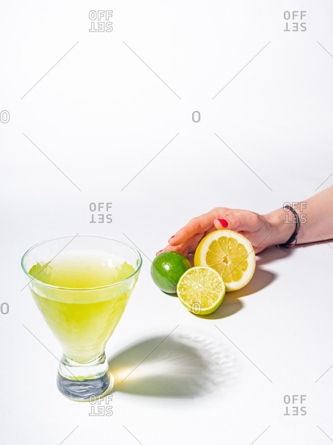 Woman crop hands holding sliced of lemon and limes near a glass of yellow lemonade drink on white background
