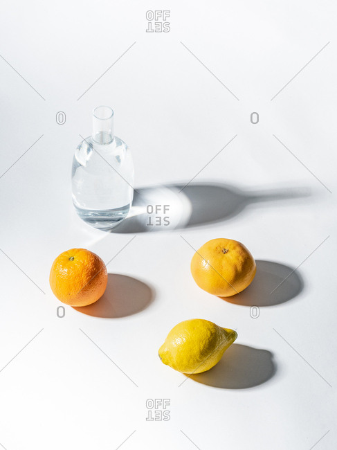 Ripe oranges near clear jar of water on white background