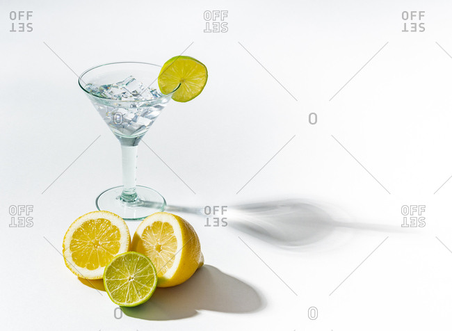 Glass of drink full of ice cubes and sliced orange lime and lemon on white background