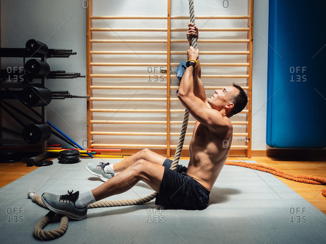 Side view of shirtless muscular sportsman climbing up rope while exercising in modern gym