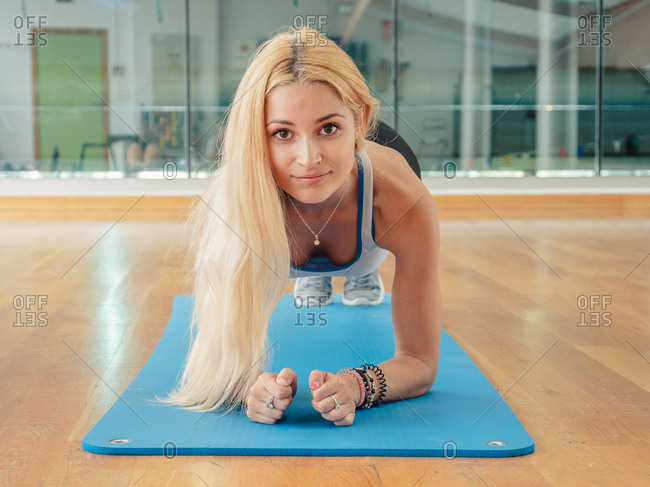 Slim woman in sportswear looking at camera while doing plank on mat in gym