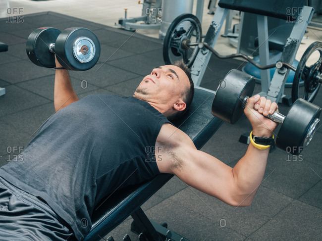 Side view of muscular adult male doing exercise with dumbbells while lying on bench in gym