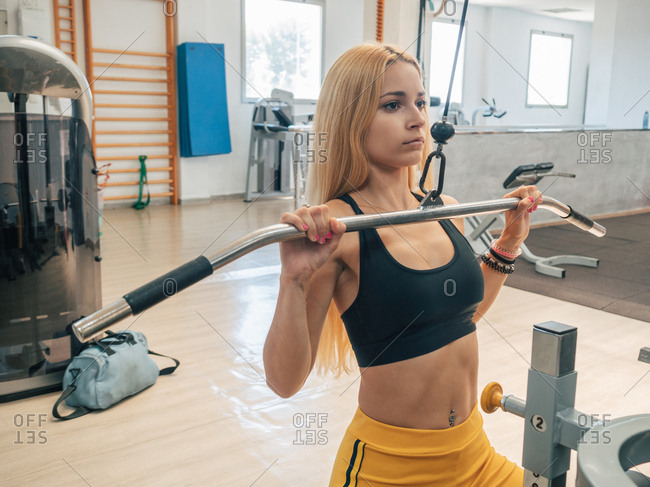 Slim sportswoman pulling down bar of exercise machine during training in gym looking at camera
