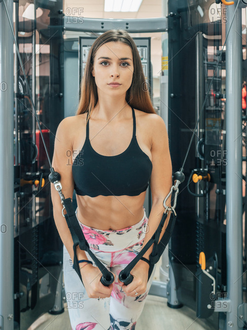 Athletic young lady in sportswear looking at camera and doing chest flies exercise with machine training in gym