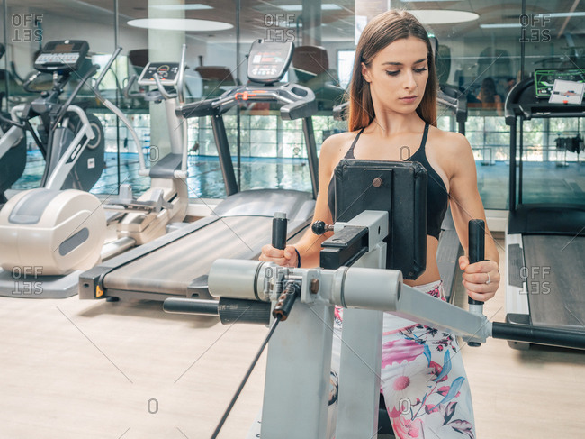 Focused fit woman in sportswear looking away while exercising on seated row machine in gym
