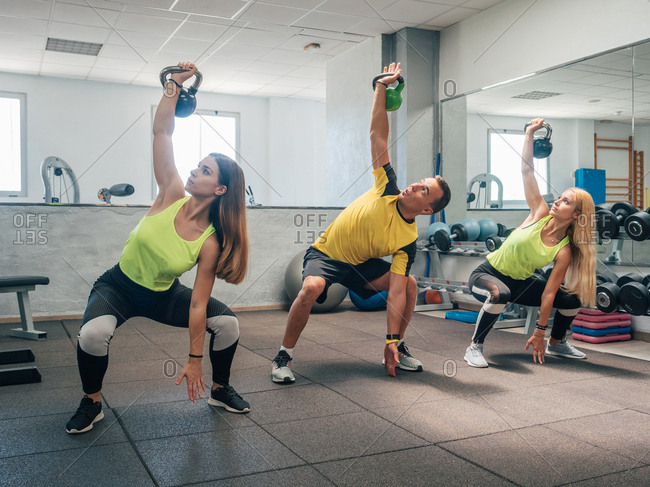 Strong man and women lifting kettlebells over head and doing squats during workout in gym