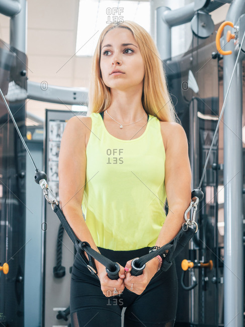 Athletic young lady in sportswear looking away and doing chest flies exercise with machine training in gym