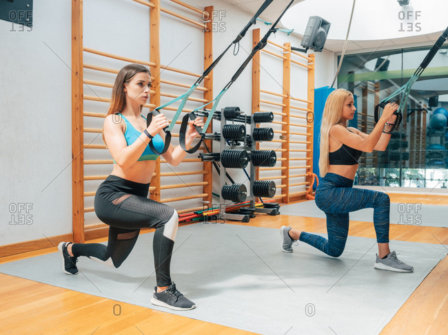 Side view of young confident women doing squats while having suspension training with ropes in modern gym and looking at camera