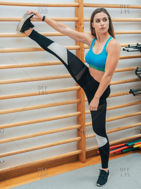 Slim young female in sportswear leaning leg on gymnastic ladder and looking away while doing stretching exercise in gym