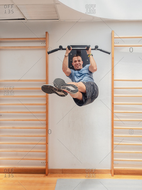 Strong guy in sportswear lifting legs and twisting body while hanging on bars and smiling during workout in gym