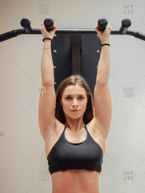 Muscular female athlete in sports bra looking at camera while hanging on bars during training in gym