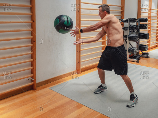 Powerful shirtless male throwing heavy ball against wall during fitness workout in gym