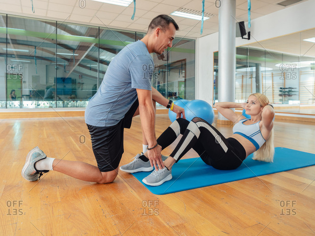 Side view of personal trainer helping young female to do abdominal crunches on floor in spacious gym