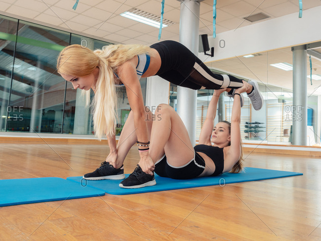 Young athletic women on mat balancing on each other while training abs together in light gym