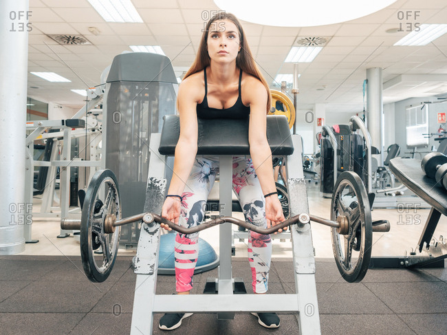 Strong woman doing bicep curls on barbell on bench in the gym
