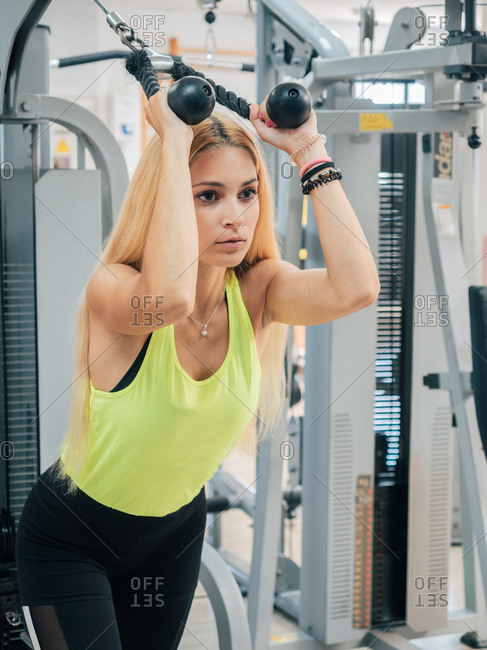 Strong young lady in sportswear pulling rope of exercise machine while training triceps and working out in modern gym