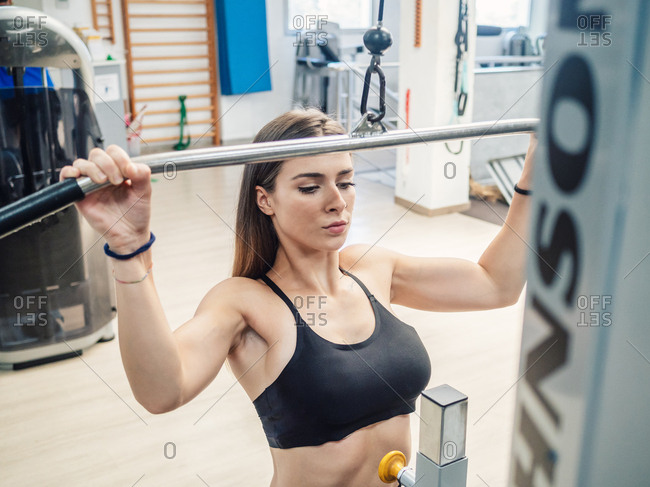 Slim sportswoman pulling down bar of exercise machine during training in gym