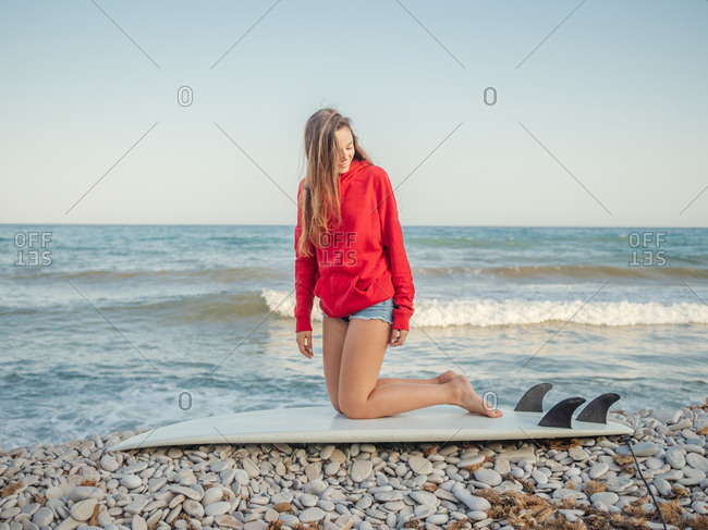 Side view of attractive smiling long haired woman in red hoodie enjoying sitting on surfboard on stony seaside